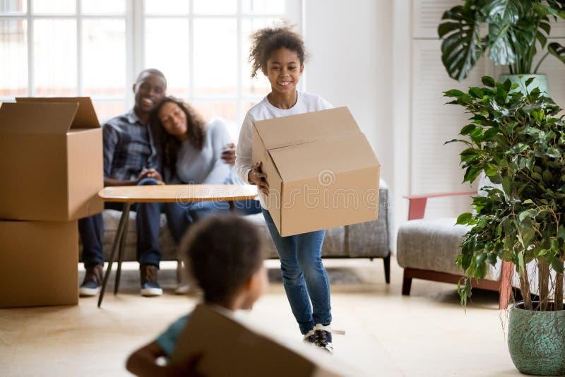 拿着箱子的激动的混合的族种孩子使用在新的家 免版税库存照片