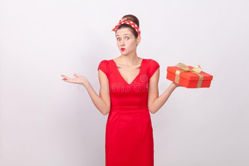 拿着箱子的迷茫,困惑的逗人喜爱的妇女,说穿上` t知道 库存照片