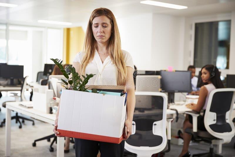 拿着箱子财产的被解雇的女性雇员在办公室 库存图片
