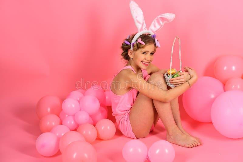 拿着篮子用复活节彩蛋的女孩佩带的兔宝宝耳朵 库存图片