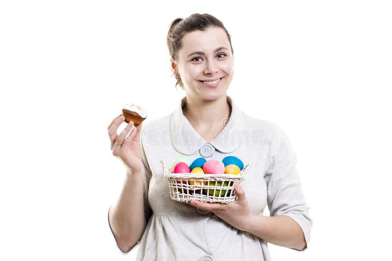 拿着篮子用复活节彩蛋的女孩隔绝在白色背景 多彩多姿的复活节彩蛋在女孩的手上 库存照片