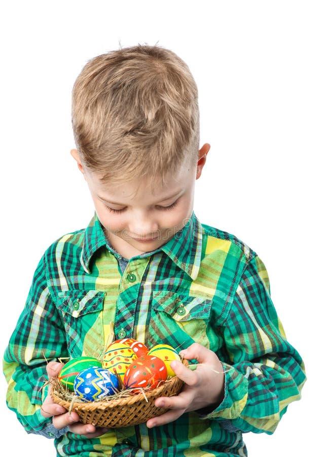 拿着篮子用复活节彩蛋的愉快的男孩 查出在白色 免版税库存图片