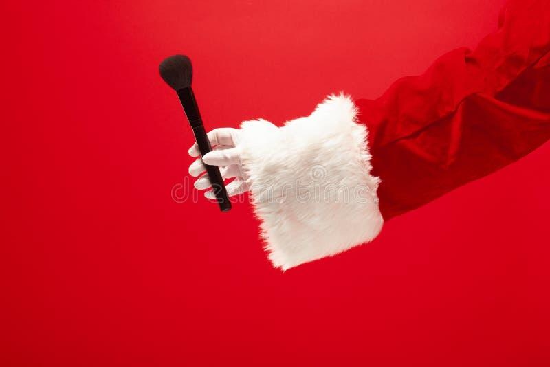 拿着粉末的圣诞老人项目的手构成刷子在红色背景 免版税图库摄影