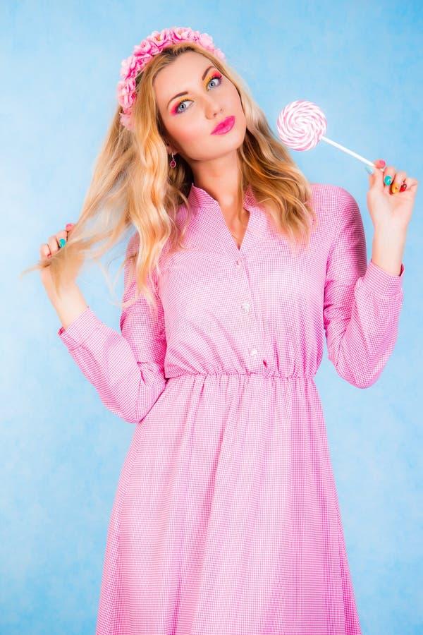 拿着糖果的一件长的桃红色礼服的逗人喜爱的少妇 图库摄影