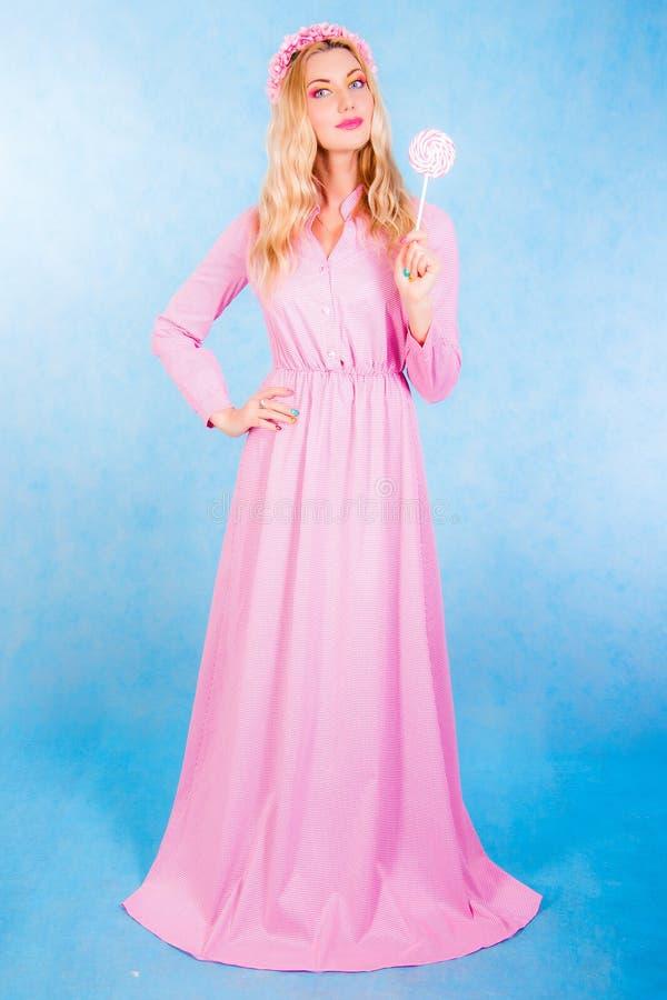 拿着糖果的一件长的桃红色礼服的逗人喜爱的少妇 库存图片