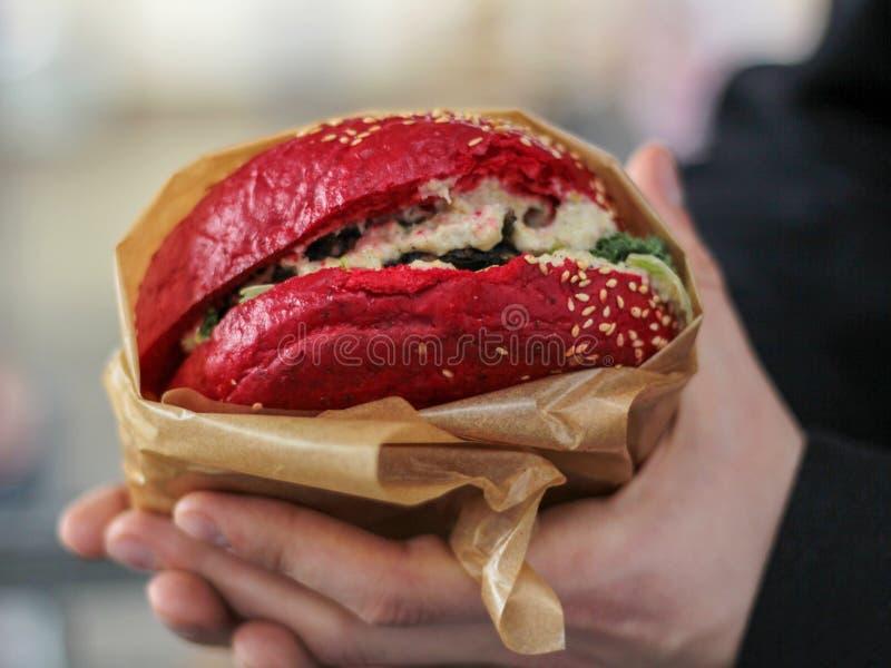 拿着素食主义者汉堡的手 免版税库存图片