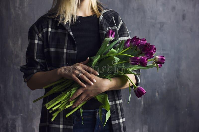 拿着紫色特里郁金香的花束格子花呢上衣的少妇 库存照片