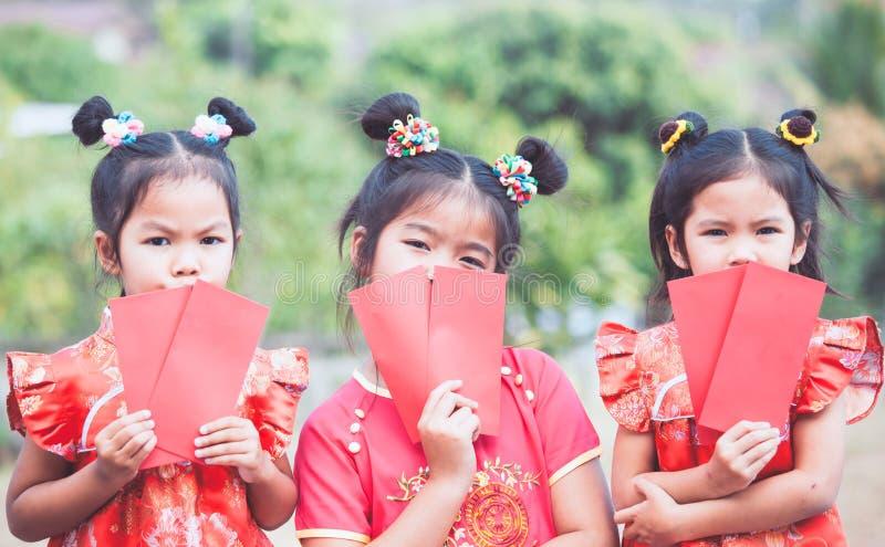 拿着红色信封的三个逗人喜爱的亚裔儿童女孩 库存照片