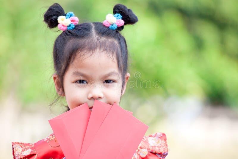 拿着红色信封的逗人喜爱的亚裔儿童女孩 免版税库存照片
