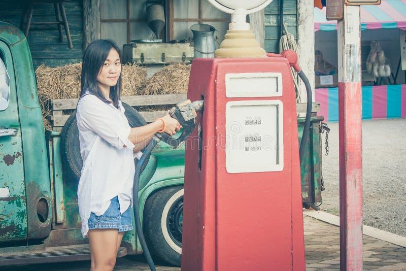拿着红色加油泵喷管有减速火箭的汽车背景的画象亚裔妇女在乡下 库存照片