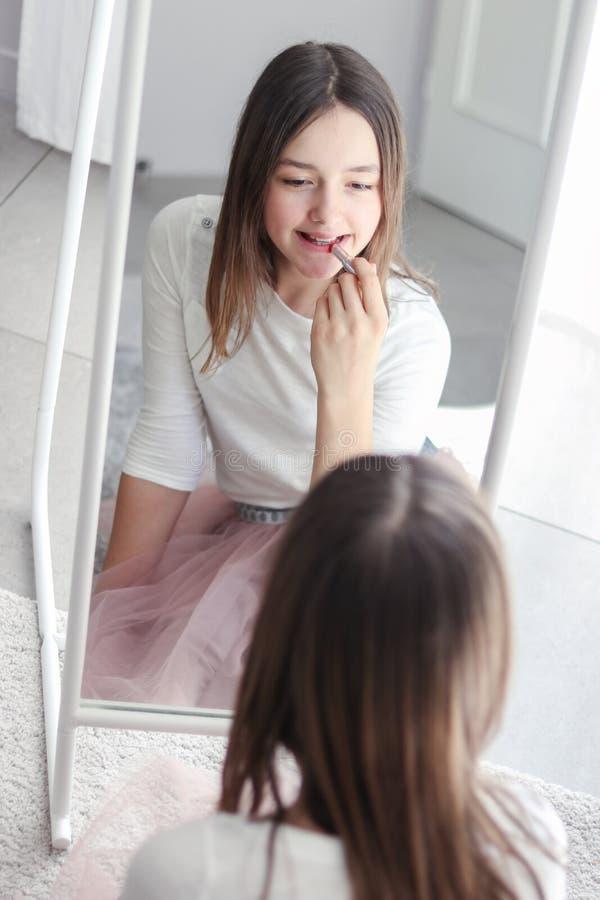 拿着红色口红的俏丽的非离子活性剂女孩胭脂嘴唇看大镜子 库存照片