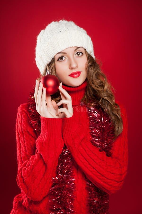 拿着红色圣诞节球的深色的女孩 免版税图库摄影