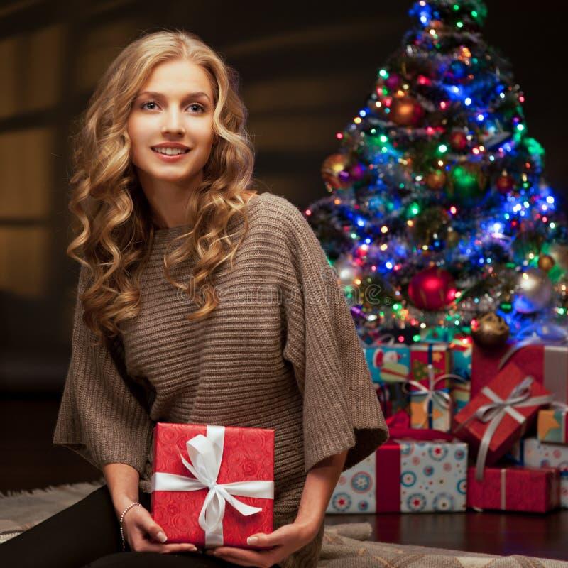 拿着红色圣诞节礼品的新微笑的妇女 免版税库存照片