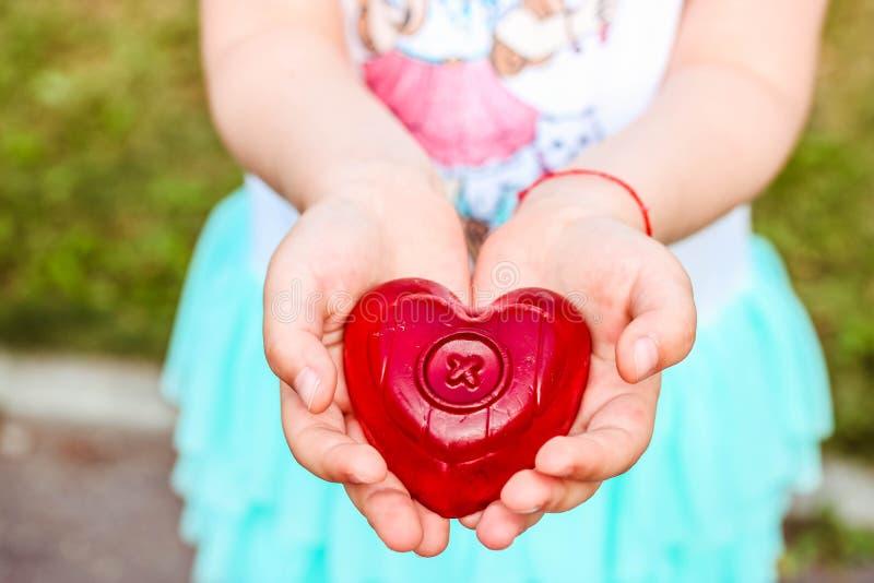 拿着红色婴孩肥皂的女孩以心脏的形式 健康lifistyle概念或爱概念 库存图片