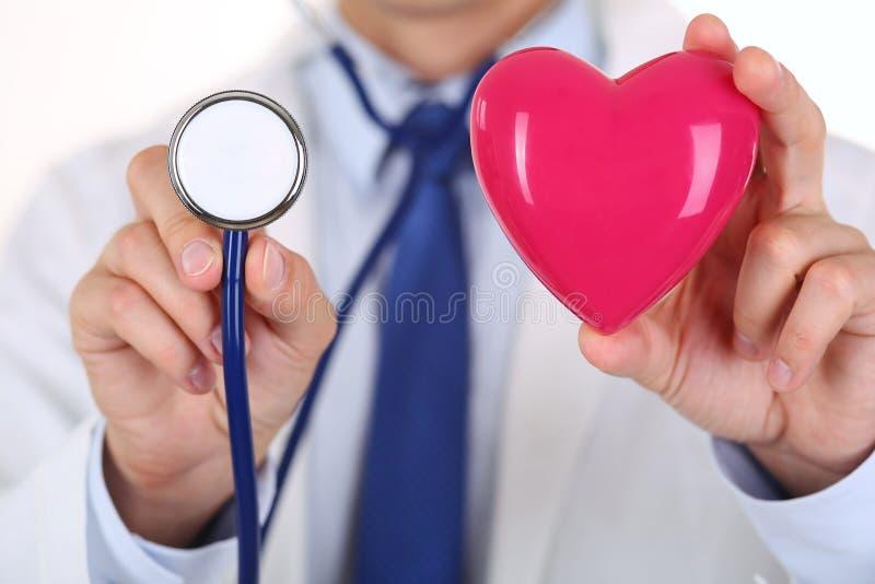 拿着红色心脏和听诊器的男性医学医生