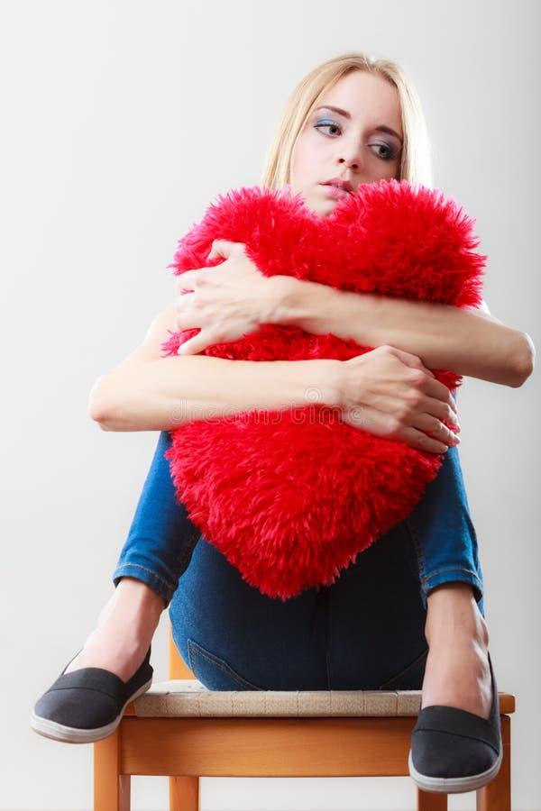 拿着红色心脏枕头的哀伤的不快乐的妇女 免版税图库摄影