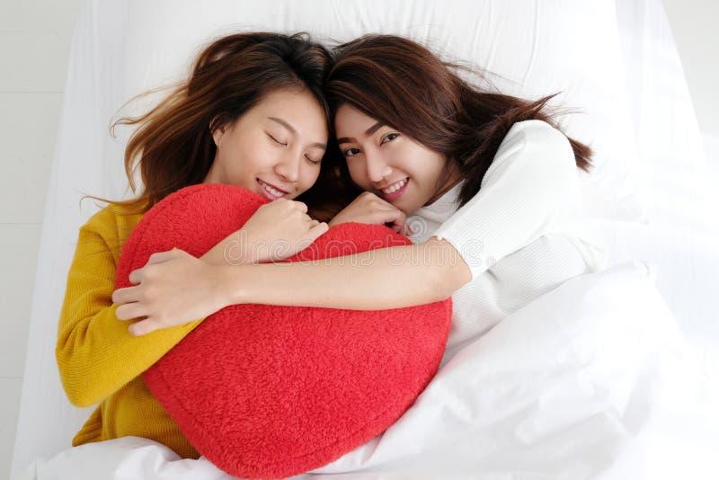 拿着红色心脏的年轻逗人喜爱的亚洲女同性恋者一起塑造杨柳 免版税图库摄影
