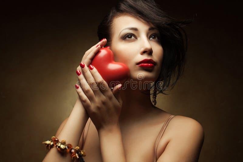 拿着红色心脏的微笑的时兴的模型画象  免版税库存图片