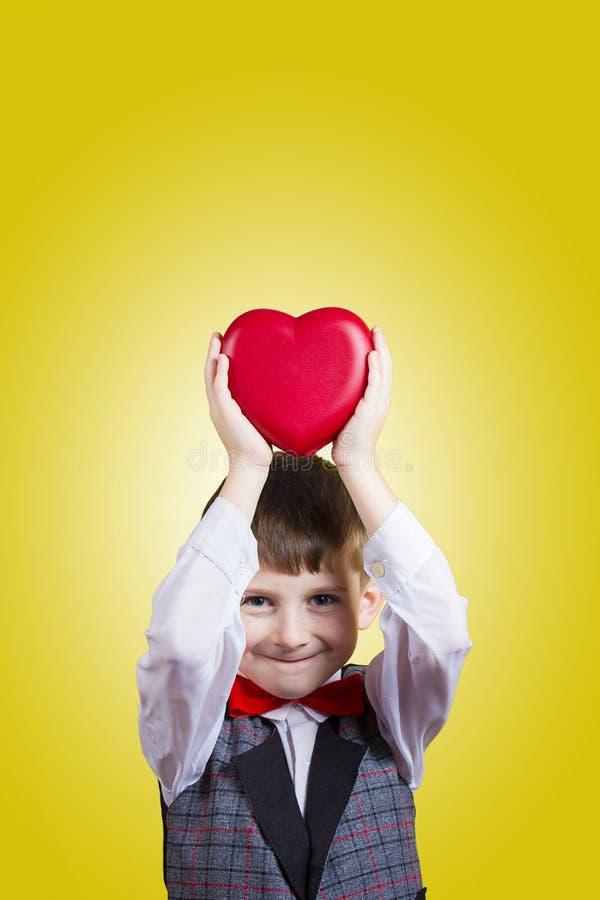 拿着红色心脏的愉快,微笑的小男孩 免版税图库摄影