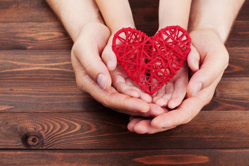 拿着红色心脏的成人和孩子移交一张木桌 家庭关系,医疗保健,小儿科心脏病学概念 库存图片