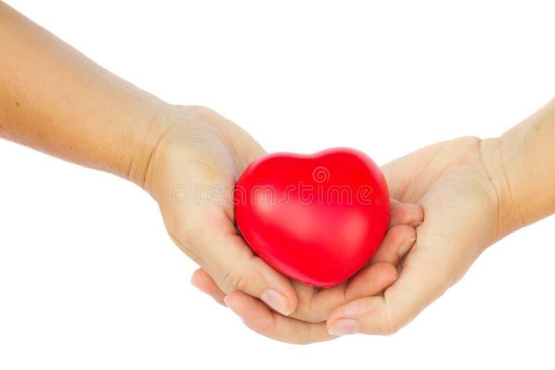 拿着红色心脏的手 免版税库存照片