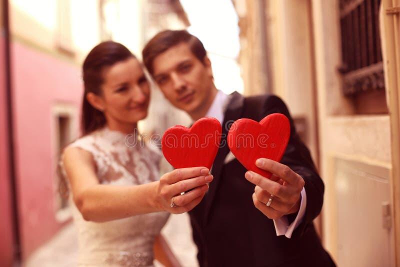 拿着红色心脏的新娘和新郎 库存照片