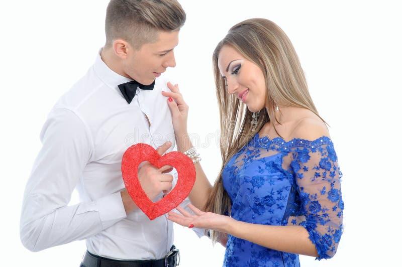 结合在一起使红色心脏的年轻可爱的夫妇 免版税库存照片
