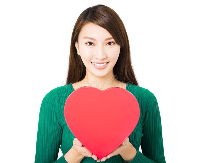 拿着红色心脏礼物盒的美丽的少妇 免版税库存照片