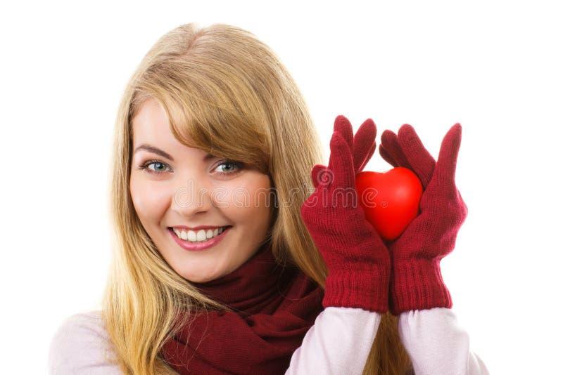 拿着红色心脏,爱的标志的羊毛手套的妇女 免版税库存照片