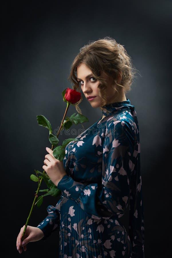拿着红色玫瑰的可爱的确信的女孩 库存图片