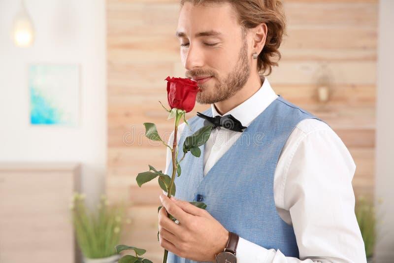 拿着红色玫瑰的礼服的帅哥 库存照片