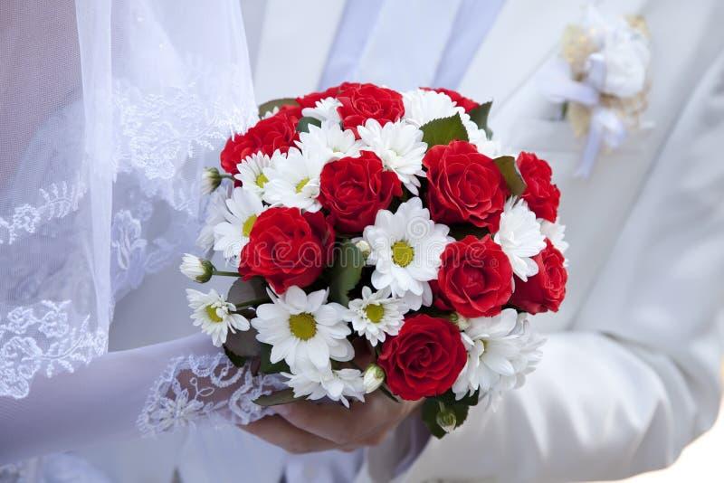 拿着红色玫瑰的美丽的花束新娘婚姻 免版税图库摄影