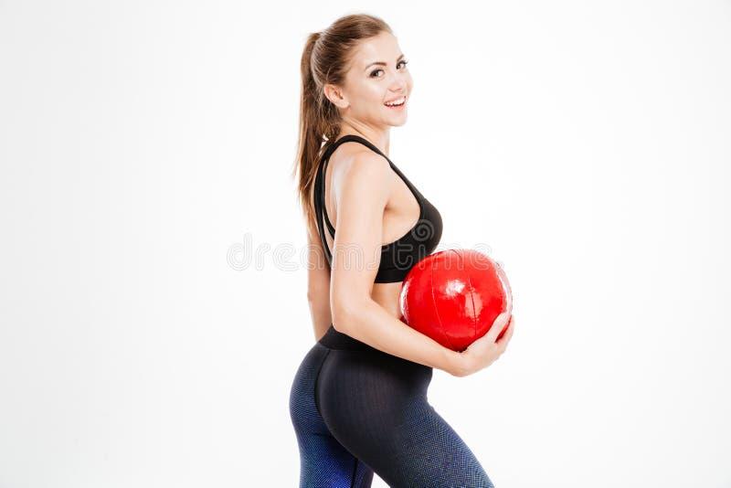 拿着红色球和看照相机的美丽的健身妇女 免版税库存图片