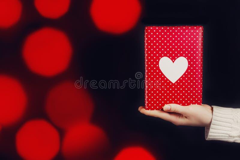 拿着红色礼物的手被隔绝在黑色 免版税库存照片