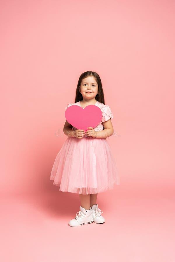 拿着红色纸心脏和微笑对照相机的薄纱礼服的笑的时尚女孩隔绝在桃红色背景 免版税库存照片