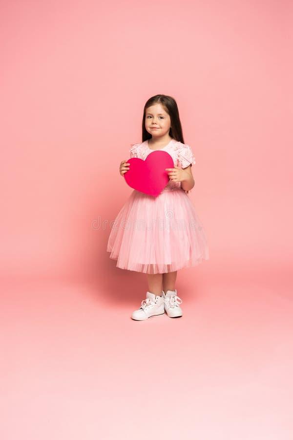 拿着红色纸心脏和微笑对照相机的薄纱礼服的笑的时尚女孩隔绝在桃红色背景 库存图片