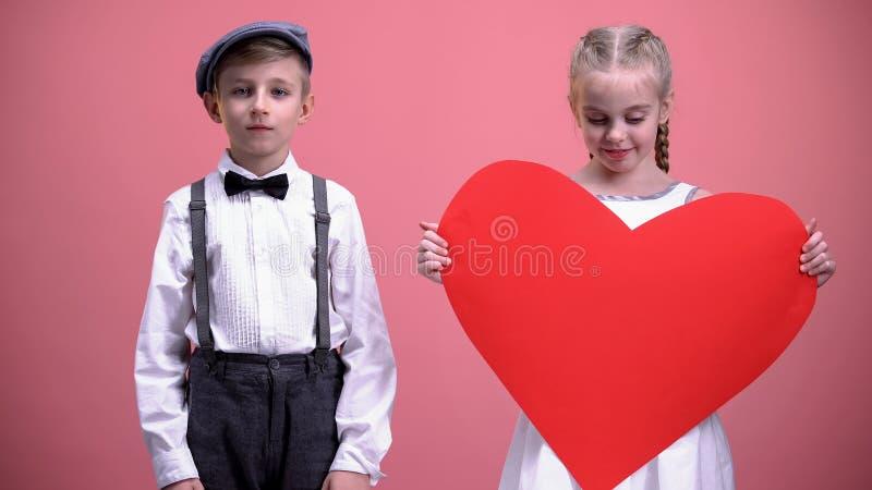 拿着红色纸心脏的少女,站立在年轻男孩附近,情人节 库存照片