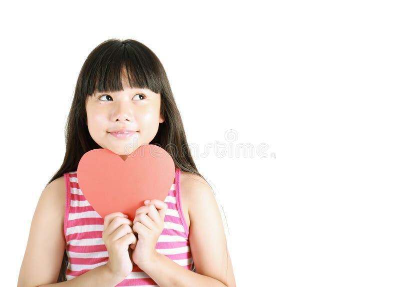 拿着红色纸心脏的逗人喜爱的矮小的亚裔女孩 免版税库存图片