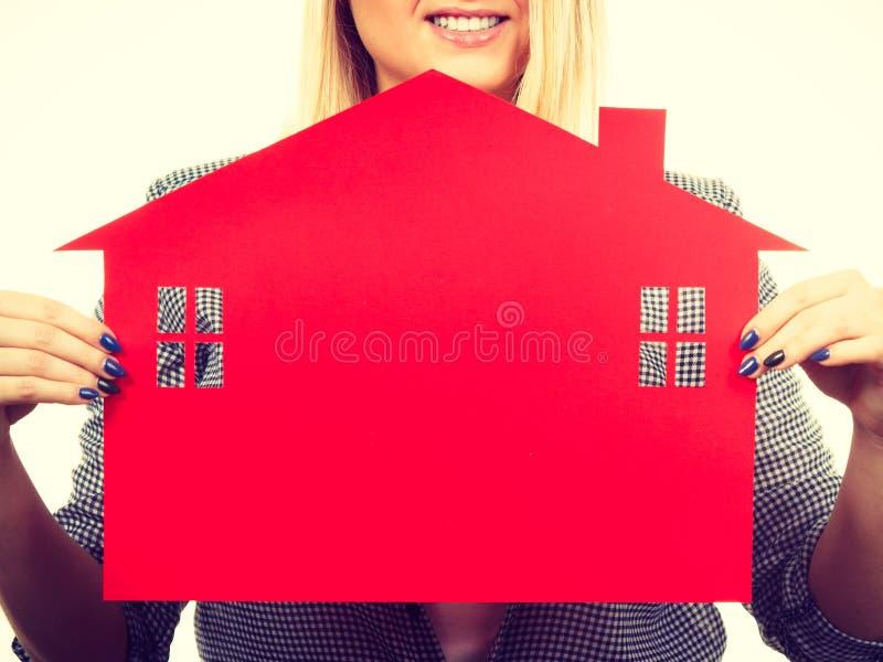 拿着红色纸房子的愉快的妇女 免版税库存图片