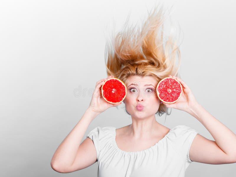拿着红色葡萄柚的妇女有疯狂的被风吹头发 库存图片