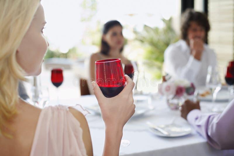 拿着红色葡萄酒杯的妇女在晚餐会 免版税库存照片