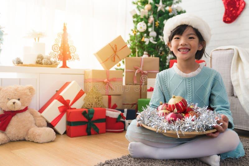 拿着红色装饰的板材逗人喜爱的亚裔女孩 免版税图库摄影