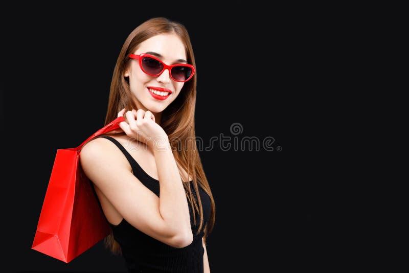 拿着红色购物袋的性感的富有的妇女 免版税库存图片