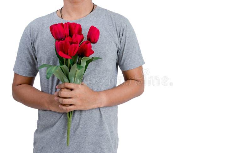 拿着红色郁金香花的被隔绝的亚裔年轻人 免版税库存图片