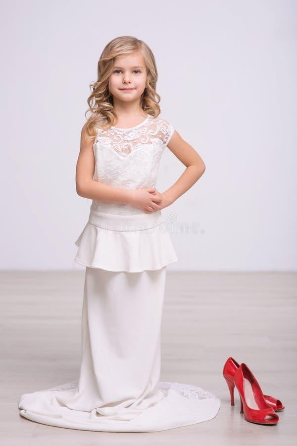 拿着红色鞋子的快乐的小女孩 库存图片