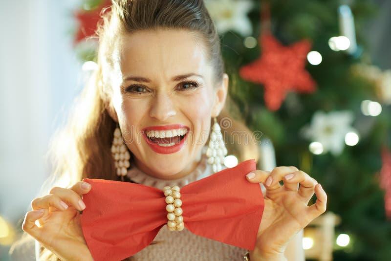 拿着红色饭裆的微笑的时髦主妇当蝶形领结 免版税库存照片