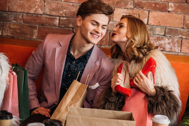 拿着红色高跟鞋和亲吻微笑的男朋友的美丽的少妇 免版税图库摄影