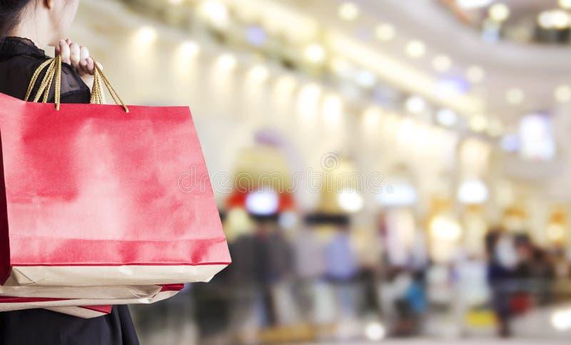 拿着红色购物袋的少妇在百货商店 免版税图库摄影
