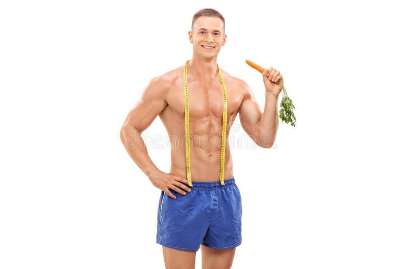 拿着红萝卜的年轻男性运动员 图库摄影