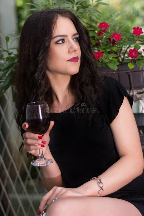 拿着红葡萄酒玻璃手中和放松在庭院公园的女性 图库摄影